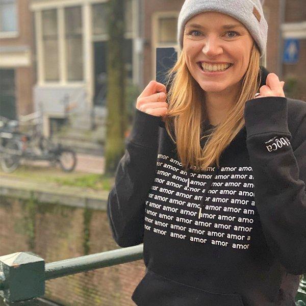 model buiten vrolijk zwarte trui met witte tekst