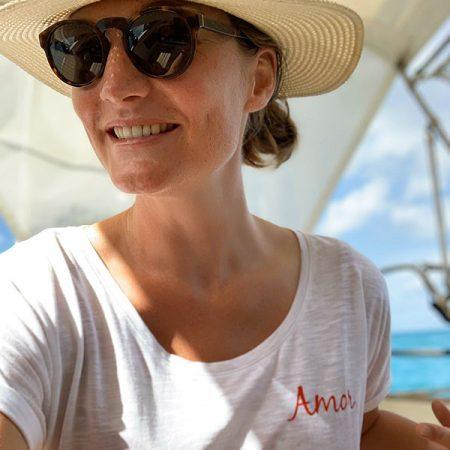 vrouw op boot met wit shirt en rode letters AMOR