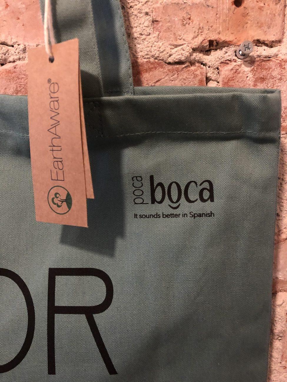 Groene tas met logo Poca Boca Amor por Favor voor muur