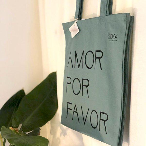 Groene tas Amor por Favor voor muur bij plant