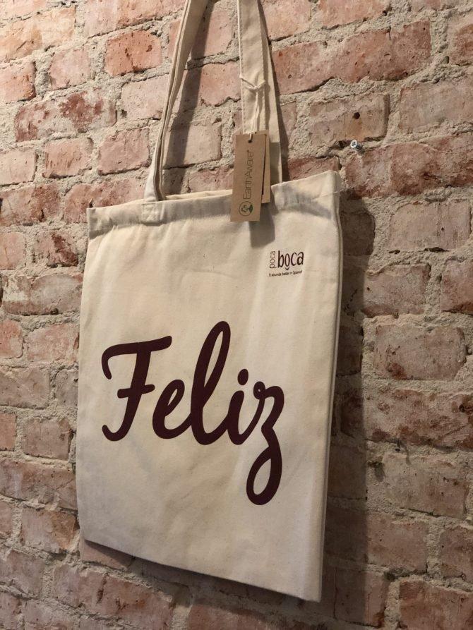 Beige tas rode tekst Feliz voor muur