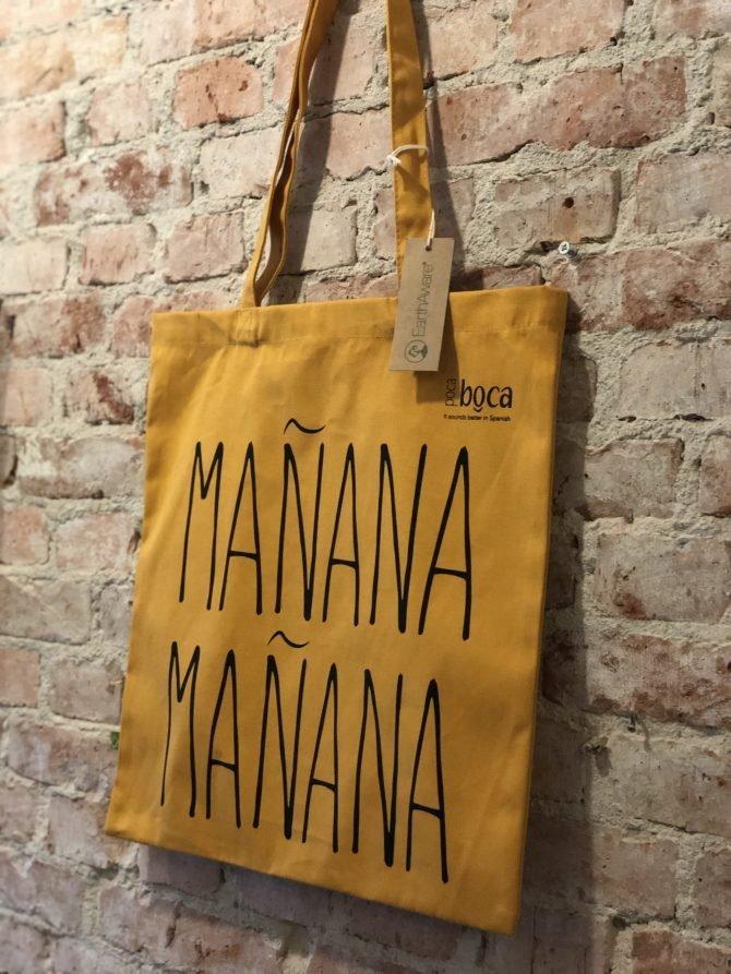 Gele tas met zwarte tekst MANANA MANANA voor muur met